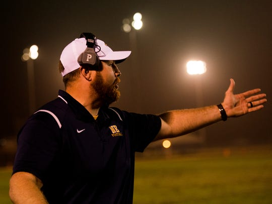 Northeast's head coach Chad Watson yells after a play