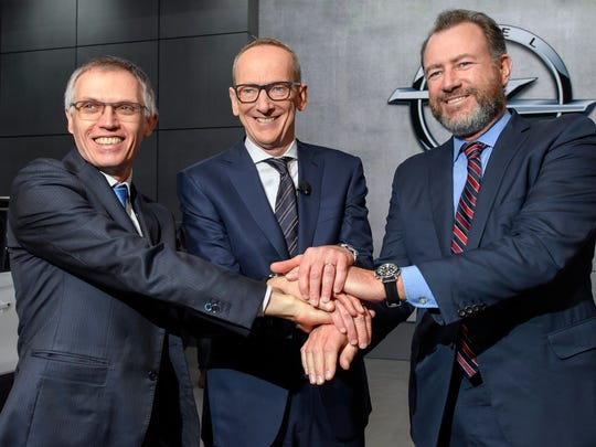Fro left, Carlos Tavares, CEO of PSA Peugeot Citroen, Karl-Thomas Neumann, CEO of Opel Group and Dan Ammann, President of GM, shake hands during the presentation of the new Opel Insignia car during the press day at the 87th Geneva International Motor Show in Geneva, Switzerland, March 7, 2017.