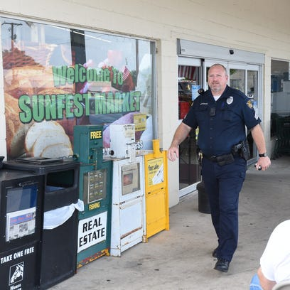 Sgt. Everett Uchtman of the Gassvile Police Department leaves Sunfest Market Thursday as police investigated a bomb threat. Thursday's threat was the second bomb threat Gassvile police have dealt with this week.