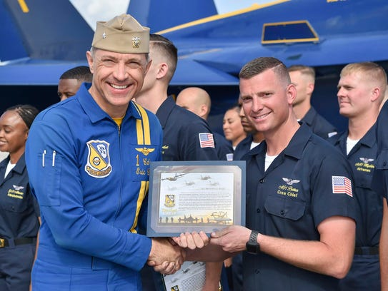 Aviation Ordnanceman 1st Class Brandon Bates (right) from Cocoa Beach receives his Blue Angels crest from Cmdr. Eric Doyle, Blue Angels flight leader, last month at Naval Air Facility El Centro in California.