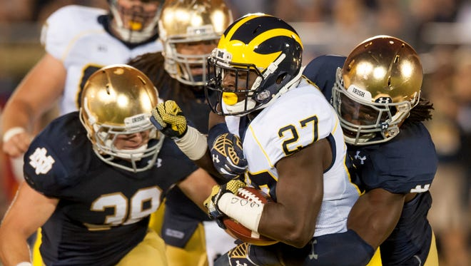 Michigan running back Derrick Green is wrapped up by the Notre Dame defense in a game last season.