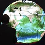 A conference attendee looks at a projection of Earth on the opening day of the COP 21 United Nations conference on climate change on Nov. 30, 2015, in Le Bourget, on the outskirts of Paris.