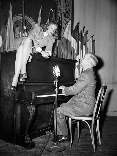 In this Feb. 10, 1945 file photo, Vice President Harry S. Truman plays the piano as actress Lauren Bacall lies on top of it during her appearance at the National Press Club canteen in Washington. Bacall, who died Tuesday, Aug.12, 2014, at 89, was a fashion darling of a unique sort. A model at 16, later a pal of Yves Saint Laurent and a frequent wearer of designs by Norman Norell.