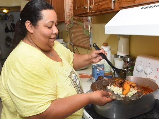 Hilda Elliott-Brooks serves up a plate of catfish in
