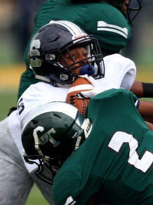Detroit Cass Tech's Donovan Johnson tackles Southfield's Josh Pickens during the first half of Cass Tech's win Saturday at Wayne State.