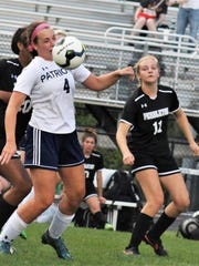Powdersville's Taylor Dierks (4) looks to control a ball while  Pendleton's Savannah Stuettgen.