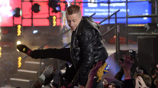 Macklemore dives into the crowd as thousands of revelers gather in New York's Times Square to celebrate the ball drop at the annual New Year's Eve celebration.