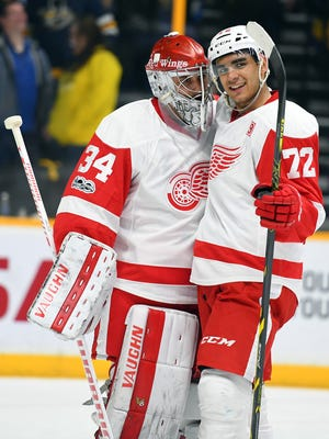 Red Wings goalie Petr Mrazek celebrates with center Andreas Athanasiou after a win against the Nashville Predators on Feb. 4, 2017.
