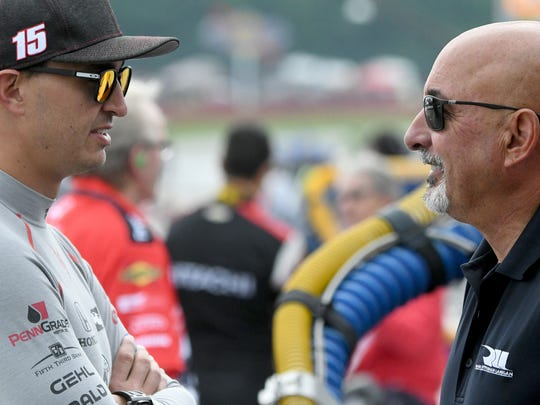 IndyCar driver Graham Rahal chats with father and team owner Bobby Rahal.