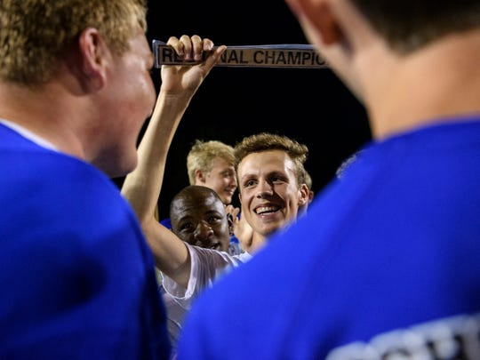 Memorial's Matthew Schadler celebrates his regional title win with the rest of the track and field team at Central Stadium in Evansville, Ind., Thursday, May 24, 2018. The team won their first regional track title in school history.