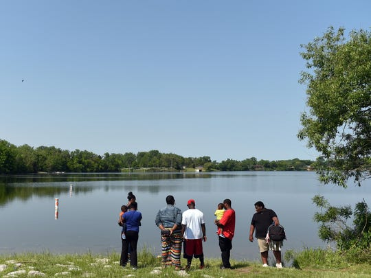 Tonya Jackson's family members stand on the shoreline of Ford Lake off Bridge Rd. in Ypsilanti Township on Thursdayas investigators search for evidence on Thursday.