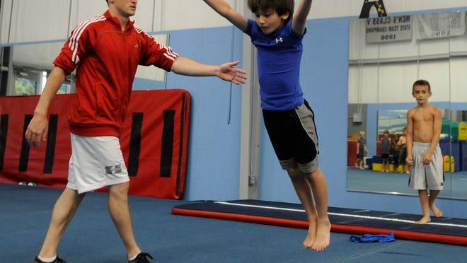 Former Olympian Morgan Hamm works with the boys gymnastics class at Armory Athletics on Thursday.