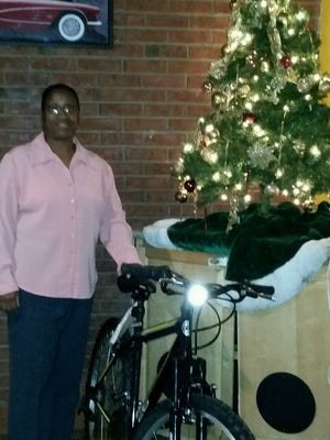 Divenus Parker, president of Stars on Sun #6, stands with one of the bicycles her organization will give away Sunday to youths being served by the Juvenile Probation Department.