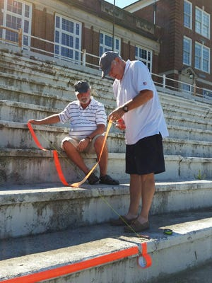 Dennis Latta and Herb Foster carefully measure out the tape needed to create a large 66 on the cement steps of the former Robert E. Lee High School for their 1966 class reunion.
