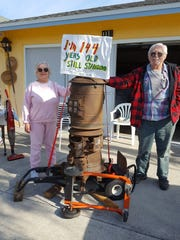 Jean and Joe Kowinsky show off their 144-year-old antique parlor stove being offered in the 30th annual Isles of Capri All-Island Yard Sale.