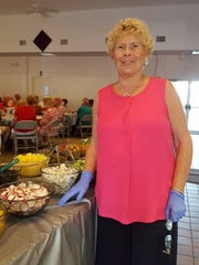 Linda Addy, standing beside the infamous salad bar that offered 24 toppings, not only served as chair of the Sweetheart Banquet but also made all of the table center pieces by hand from toilet paper and towel rolls.