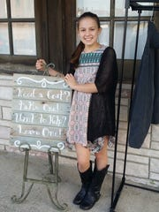 Maddie Harter, 14, set up a coat rack outside of the Shop of Pleasant View for a community service project.