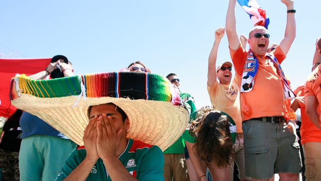 A Mexico soccer fan buries his face in his hands after Holland scores their second goal of the game to beat Mexico 2-1 in their round of 16 World Cup match on Sunday, June, 29, 2014.
