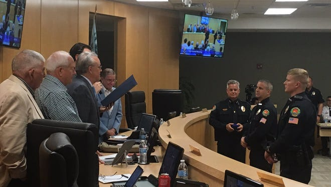 """The Marco Island City Council recognizes police officers Willem Hernandez and Jeffrey Stafford for """"taking extraordinary and heroic rescue measures to save an individual's life"""" at its meeting on March 5, 2018."""