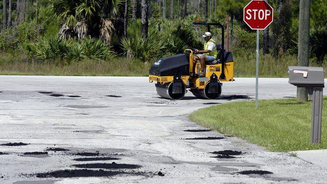 Roads in need of repair have long been a concern in Palm Bay. In this 2010 photo, a public works employee rolls over freshly filled potholes on the city's southeast side.
