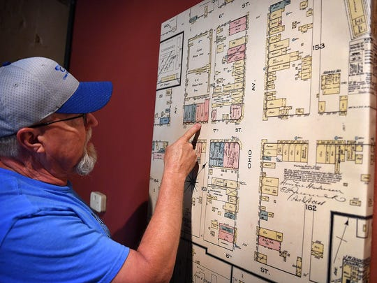 Bill Weske, co-owner of Hook & Ladder Coffees & Winery, looks over a map of downtown Wichita Falls from the 1800s that shows the business location on Seventh Street, one of the oldest buildings in the city.