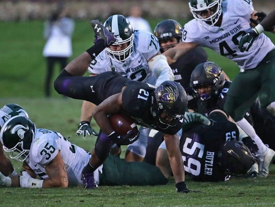 Northwestern's Justin Jackson keeps his balance as he runs for a first down during Saturday's game. Jackson had 92 yards of total offense against the Spartans.