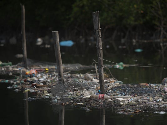 "FILE - In this Feb. 28, 2015 file photo, trash floats on the water along a fence line in the Guanabara Bay in Rio de Janeiro, Brazil. The world governing body of sailing threaten Friday, April 24, 2015, to move events for the Rio 2016 Olympics out of the city's polluted Guanabara Bay unless ""a whole lot more is done very quickly"" to clear the venue of floating debris and sewage. (AP Photo/Leo Correa, File)"