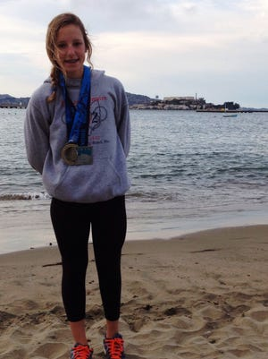 Emma Savarese on Chrissy Beach wearing her medals from the Alcatraz Challenge Swim.