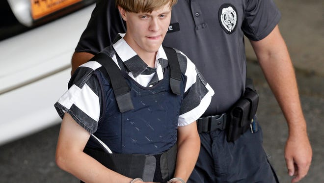 In this June 18, 2015 file photo, Charleston, S.C., shooting suspect Dylann Storm Roof is escorted from the Cleveland County Courthouse in Shelby, N.C. When nine black churchgoers in Charleston were massacred by Roof, a white man with Confederate sympathies, the city stayed calm and the victims' families offered examples of grace and forgiveness. Now that church shooting suspect Roof has been convicted in a federal death penalty trial, some say the parade of killings of black people feels at odds with the call to forgive.