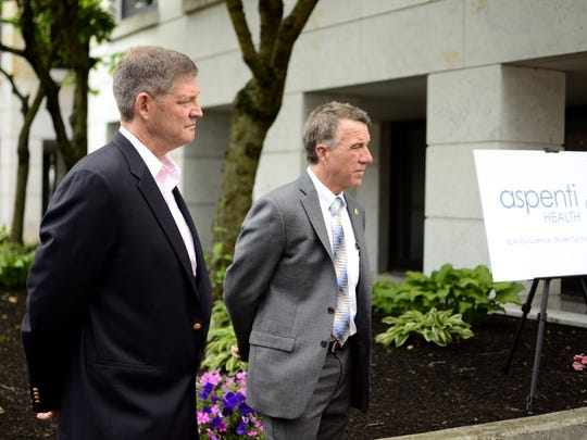 Chris Powell, CEO of Aspenti Health, and Gov. Phil Scott attend a news conference about the future of the drug-testing company formerly known as Burlington Labs on July 10, 2017.