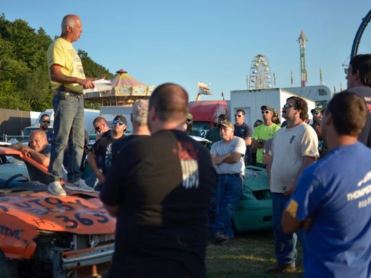 Ron Cummins, an official for JM Motorsports, speaks to drivers about rules and safety tips for the Burnett Scrap Metal Double Figure 8 Race and Demolition Derby at the Champlain Valley Fair in Essex Junction on August 30, 2017.