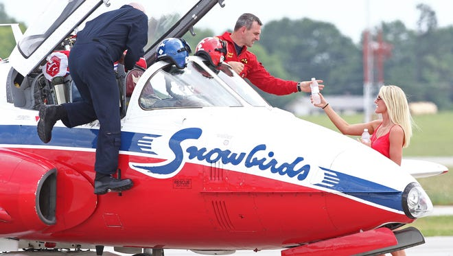 Hailey Gunderson, right, of Anderson hands plane one pilot Maj. Patrick Gobeil, of The Royal Canadian Snowbirds, a bottle of water as the team arrived a day before Wednesday's Anderson Regional Air Show in 2015.