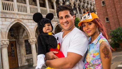 "TV personality Nicole ""Snooki"" Polizzi, right, from ""Jersey Shore,"" with her fiance, Jionni LaValle, and their 1-year-old son, Lorenzo, inside the Italy pavilion in the Epcot theme park, in this Sept. 27, 2013 file photo taken at Walt Disney World in Lake Buena Vista, Fla., and released by Disney. The cast member of the reality series ""Jersey Shore"" and ""Snooki and JWoww"" spinoff intends to marry her fiance Jionni LaValle at the Venetian banquet hall in Garfield, N.J., in the fall 2014."