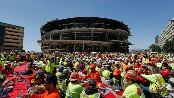In this April 7, 2015, file photo, construction works eat lunch by an MGM arena being built behind the New York-New York casino-hotel in Las Vegas.