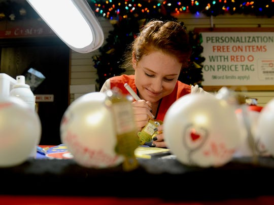Coryn Houser works on personalizing ornaments for customers