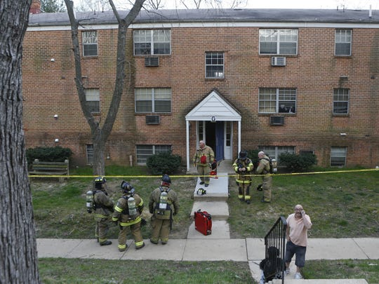 Firefighters respond to The Evergreen Apartments at Riverfront Heights near Elsmere on March 25. Four people were found dead in the apartment complex.