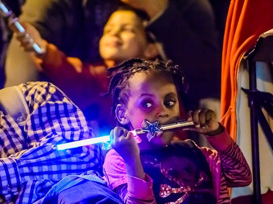 Evette Owens ,4, plays with a light wand as she waits for the Silver Bells In The City parade to begin.