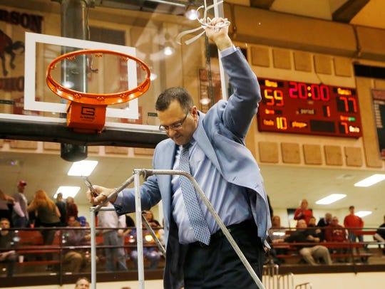 Central Catholic head coach Dave Barrett cuts down
