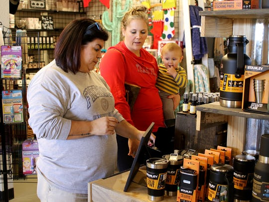 Clarissa Frerich, left, Stevi Arredondo and her son Jace look at scented products during Small Business Saturday at The Loft Marketplace.