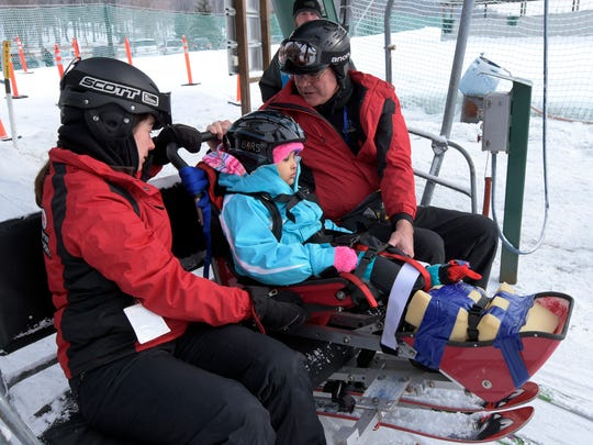 Amyiah Ferguson, 4, of York City, boards a lift with ski volunteers Tim Collard of Westminster and Sarah Bacon of Baltimore, left, during an adaptive skiing event at Roundtop Mountain Resort Friday, Feb. 9, 2018. The event is designed to allow those with physical handicaps to experience skiing. It was sponsored by Ability Prosthetics and Orthotics, Hershey Medical Center Rehabilitation and Baltimore Adaptive Recreation and Sports. Two half-day sessions drew about a dozen participants. Bill Kalina photo