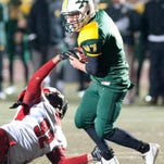 Manual Crimsons' defensive end Derek Dorsey who falls as he tries to tackle St. Xavier Tigers' running back Samuel Taylor, reaches in to try to dislodge the ball as St. X takes on Manual in a 6a playoff game. 14 November 2014