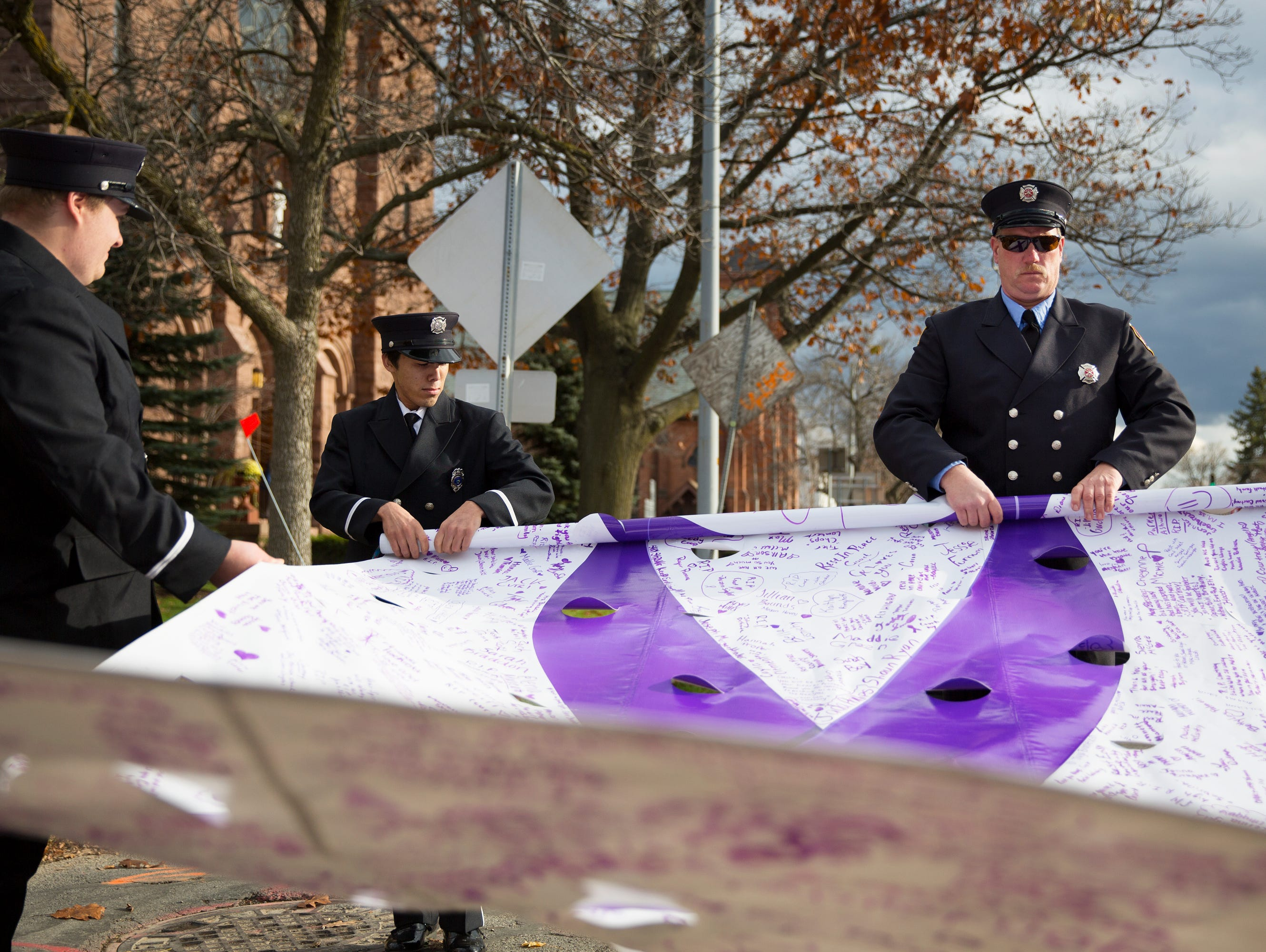 Farmington firefighter Tyler Whitcomb and Canandaigua firefighter Rich Bartell roll up a banner for Courtney Wagner following her funeral in Canandaigua on Saturday, November 7, 2015.