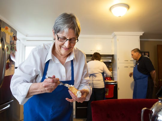 Linda Ryan fills a cannoli shell with sweet ricotta cheese filling on Saturday, December 12, 2015.