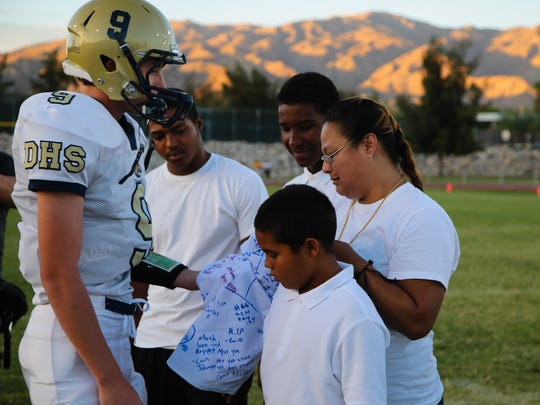 The Desert Hot Springs football caption Nathan Kelly presents a signed shirt to the family of former player Solomon Patrick at center field, Friday, August 25, 2017.  Patrick was killed in a shooting in Cathedral City this summer.