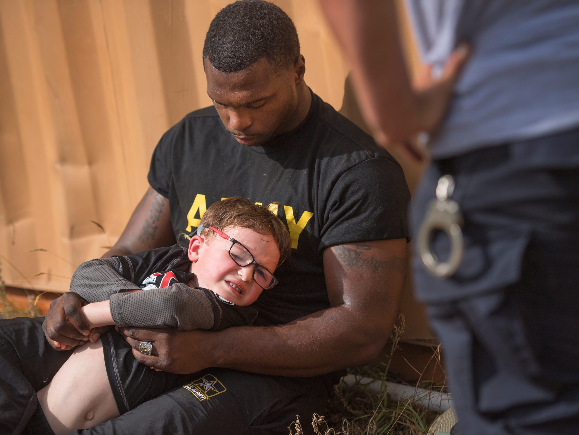 Logan Ford, 6, is held down by Sergeant Kenneth Pitts