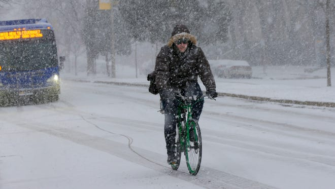 A cyclist makes his way through the snow on E. Kenwood Blvd., in Milwaukee, at the University of Wisconsin Milwaukee campus on Monday.