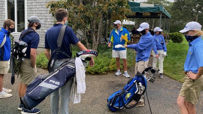 St. John Paul II golf coach Geoff Converse, center, addresses his squad and Sturgis East, all properly masked, prior to the teams' opening match Monday at the Wianno Club.