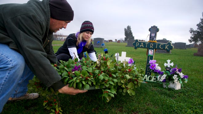 Bill Dolan, left, and his wife Dee Dolan place a flower arrangement Dee made on the grave of their son, Patrick, on Nov. 23, the one-year anniversary of his death. Patrick was killed in Baltimore.