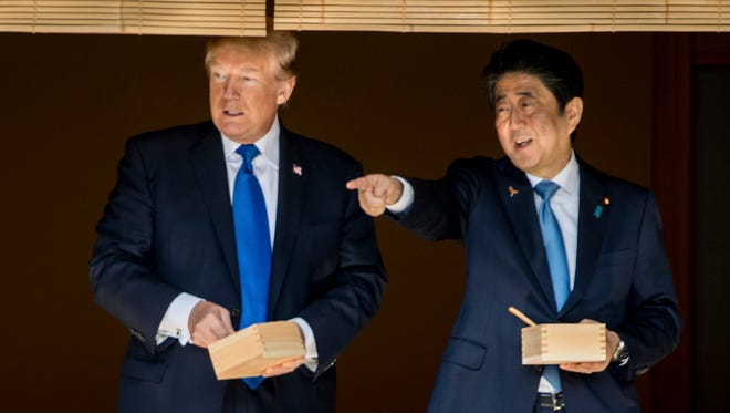 President Trump and Japanese Prime Minister Shinzo Abe speak together while feeding fish at a koi pond at the Akasaka Palace, on Nov. 6, 2017, in Tokyo.
