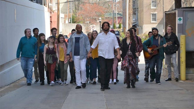Cast members Chip Holderman (Jesus) at center with Derrick DeVonne King (Peter) on left and Maggie Shermoen (Mary) on right in downtown Springfield.